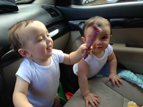 twins playing in car